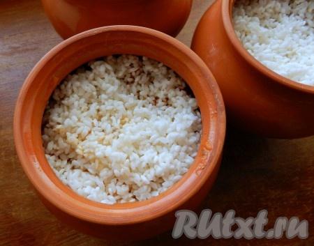 В каждый горшочек разложить промытый рис, долить горячей воды на 1 см выше уровня риса, накрыть горшочки крышками и поставить в теплую духовку, затем разогреть ее до 200 градусов и готовить свиные ребрышки в горшочках в течение 1 часа.