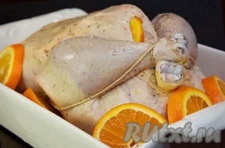11. Если у вас остались апельсины, обложите ими курицу и поставьте противень в разогретую до 180 градусов духовку.
