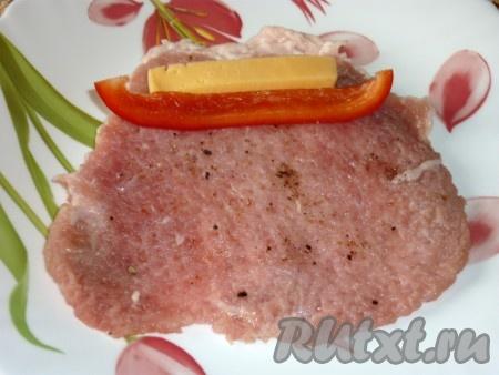 На пласт мяса положить ломтики сыра и перца.