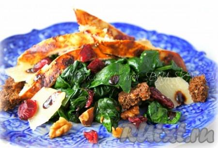 Переложить шпинат в сервировочные тарелки, добавить нарезанное куриную грудку, клюкву, сыр, сухарики и заправить салат соусом бальзамик.