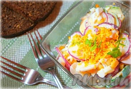 При подаче украсить салат из редиса тёртым желтком и зеленью.