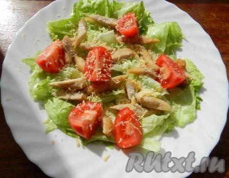 Добавить в салат помидоры, разрезанные на 4 части. Сыр натереть на терке и посыпать салат.