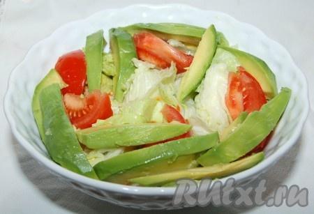 Авокадо освободить от косточки, очистить от кожуры, нарезать длинными ломтиками и добавить в миску.