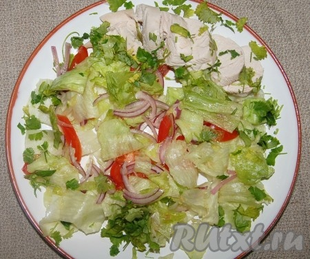 На тарелку выложить салат из миски, рядом уложить кусочки куриной грудки, посыпать зеленью кинзы.