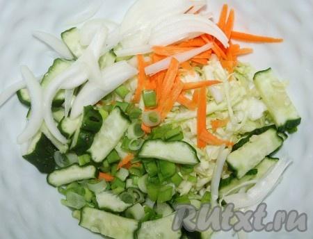Поместить капусту в миску, перетереть ее с солью, добавить тертую морковь, свежий огурец, лук репчатый и зеленый лук.