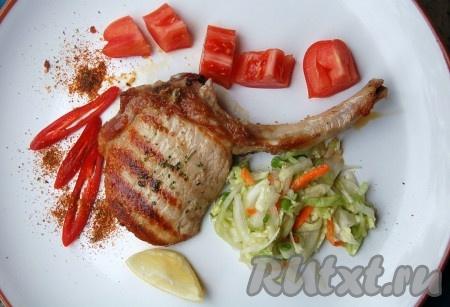 Переложить готовые свиную котлету на косточке на тарелку, добавить салат, кусочки свежих помидорчиков и ломтик лимона. Любители остренького могут добавить кусочки острого перца с острыми специями.