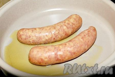 В сковороду или огнеупорную форму) налить растительное масло и выложить колбаски.