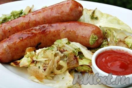 Выложить жареные колбаски с овощами на порционную тарелку, добавить соус и подавать на стол.