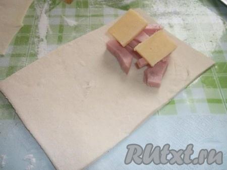 На прямоугольнички теста кладем немного колбасы и сыра.