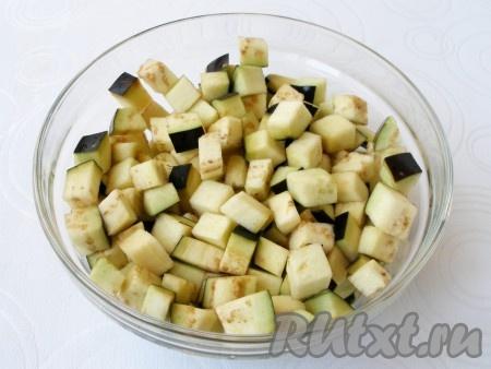 Баклажаны вымыть, нарезать небольшими кубиками и замочить в подсоленной воде на 15 минут, чтобы ушла горечь.