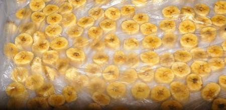 Взять полиэтиленовый пакет и вовнутрь разложить в один слой нарезанные бананы, стараясь, чтобы они не соприкасались между собой. Иначе они могут склеиться и качество их пострадает. Затем аккуратно разложить пакеты с бананами на доске, если пакетов несколько, их можно разместить друг на друге. Затем отправить в морозилку.