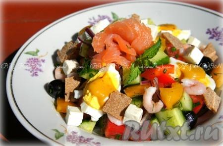 """На сервировочные тарелки выкладываем готовый салат. Каждую порцию салата украшаем четвертинками варёных яиц с горчичным соусом, добавляем красную рыбу например, в виде """"цветов"""", см. фото), креветки, сыр """"фета"""", кусочки ржаных криспов. Полить салат и рыбку небольшим количеством лимонного сока и украсить веточками мяты. Вкусный, лёгкий и очень полезный салат с креветками, помидорами, перцем и огурцами готов!"""