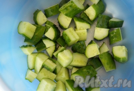 Все овощи и зелень предварительно вымыть и тщательно обсушить. Огурцы нарезать относительно крупным кубиком и отправить их в глубокую миску.