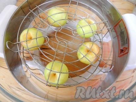 Уложить яблоки на нижнюю решетку аэрогриля, сверху установить верхнюю решетку.