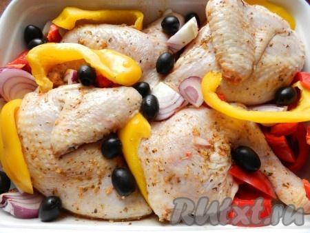 Лук и перец очистить, нарезать дольками. Выложить перец и лук к курице, добавить оливки, перемешать руками, чтобы на овощи тоже попал маринад. Поставить в разогретую до 200 градусов духовку на 1 час. В процессе запекания рекомендуется поливать кусочки курицы выделившимся соком.