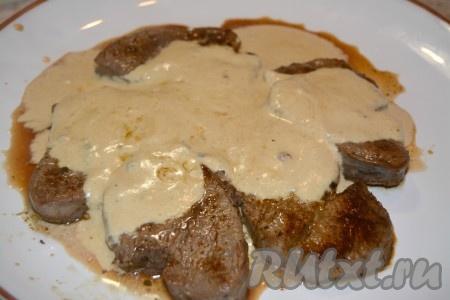 Готовым соусом из сливок залить кусочки говядины на тарелке.