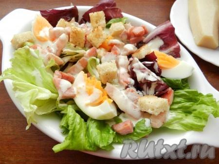 Полить салат с грудинкой соусом, посыпать сухариками.
