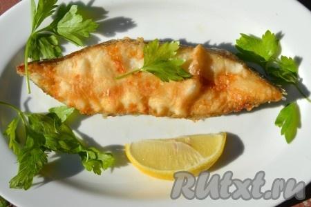 Готового жареного палтуса переложить на тарелку. Добавить ломтик лимона и веточку петрушки.