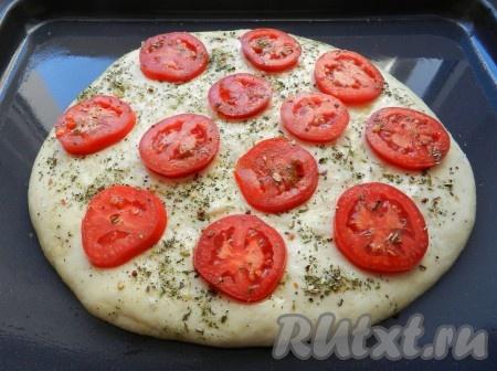 Подошедшее тесто смазать оливковым маслом. Помидоры нарезать кружочками и разложить на поверхности теста, слегка вдавить. Сверху посыпать итальянскими травами и крупной морской солью.