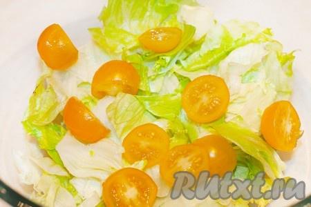 В салатник выложите листья салата и половинки помидоров черри.
