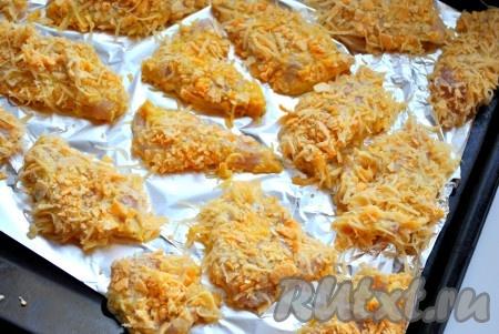 После того как куриная грудка замариновалась, обвалять кусочки курицы сначала в муке, затем окунуть в яйцо и покрыть сыром с чипсами. Выложить на застеленный фольгой противень (предварительно его лучше слегка смазать растительным маслом). Отправить куриное филе в панировке в разогретую до 200 градусов духовку до готовности (около 20 минут).