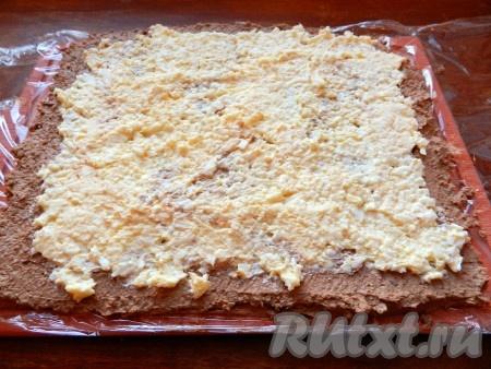 На разделочной доске расстелить пищевую пленку. Выложить сначала слой паштета, а затем слой начинки поверх него.
