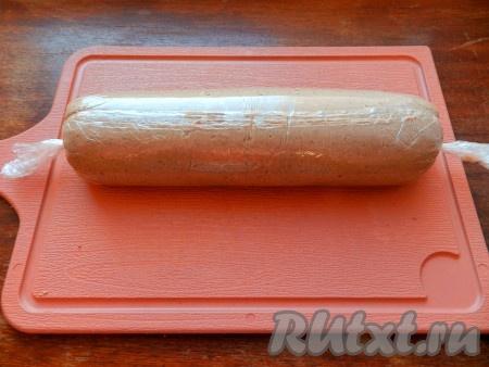 Аккуратно поднимая края пленки, свернуть рулет, закрутить и связать  концы пленки. В таком виде убрать рулет из куриной печени в холодильник на 2 часа или более.