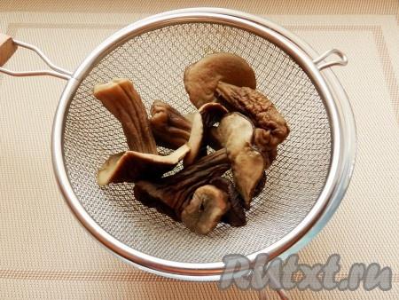 Сухие грибы промыть, замочить на ночь в чистой холодной воде. Воду слить, залить грибы свежей водой и отварить в течение 1 часа. Откинуть грибы на сито, бульон сохранить.
