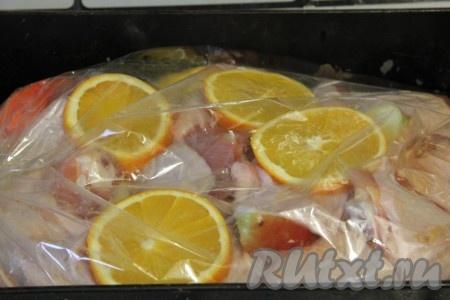 Апельсины нарезать кружочками и выложить на курицу.