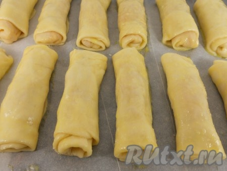 Выложить подготовленные таким образом пирожки на противень, застеленный пергаментом. Смазать желтком.