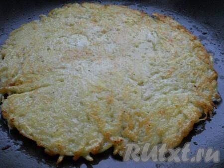 Обжарить на среднем огне до румяности, затем с помощью лопатки быстро перевернуть картофельную лепешку на другую сторону.