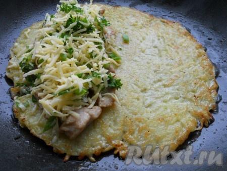 На одну сторону лепешки выложить кусочки подготовленной курицы, сверху щедро посыпать натертым на мелкой терке сыром, смешанным с измельченной зеленью.