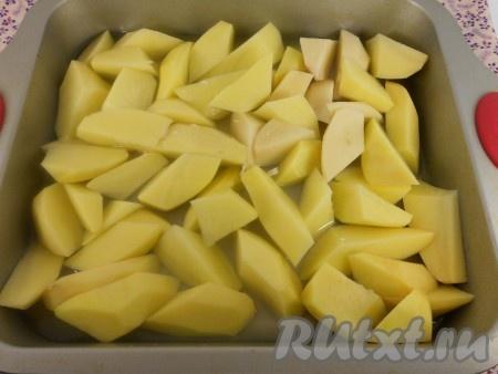 Картофель очистить и нарезать крупными дольками. Выложить в форму для запекания ровным слоем. Залить куриным бульоном.