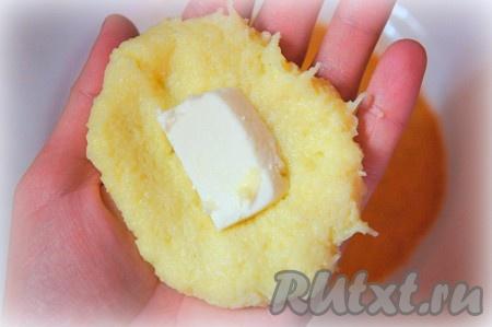 Влажными руками взять немного картофельного теста, сделать из него лепешку, в центр которой положить 1-2 кусочка сыра.