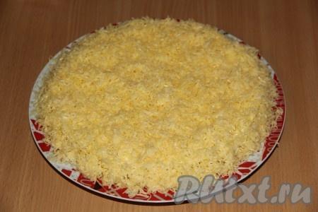 Сыр натереть на мелкой тёрке. Аккуратно снять бортики с салата. Покрыть салат щедрым слоем сыра.