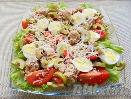 Добавить нарезанные оливки, посыпать салат тертым сыром.