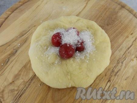 Тесто выложить на стол, присыпанный мукой, обмять немного. Оно получается отличным, &quot;дышащим&quot;! Разделить тесто на кусочки (у меня по 70 грамм - я делала большие пирожки). Руками растянуть кусочки, чтобы получились лепешки. Вишню немного разморозить, выкладывать по 3-5 ягод в центр лепешки. Сверху - по 1 чайной ложке сахара.<br />