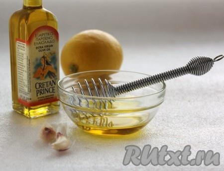 Приготовить заправку для салата из куриной грудки и овощей. Измельчить чеснок и добавить его в смесь оливкового масла и лимонного сока, размешать.