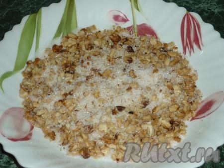 Грецкие орехи немного подсушить в духовке, измельчить скалкой (можно пропустить через мясорубку) и смешать с сахаром.