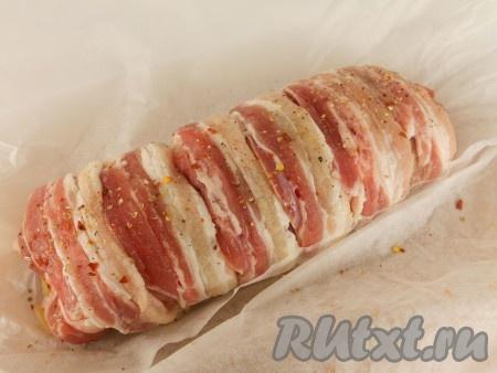 Переложить свинину с начинкой на пергаментную бумагу, поместить в форму для запекания или на противень. Сверху мясо покрыть полосками бекона, посыпать чуть солью и смесью перцев.