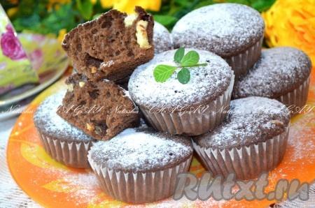 Готовые кексы остудить, достать из формочек и посыпать сахарной пудрой. Вкусные кексы с белым шоколадом можно подавать к чаю.