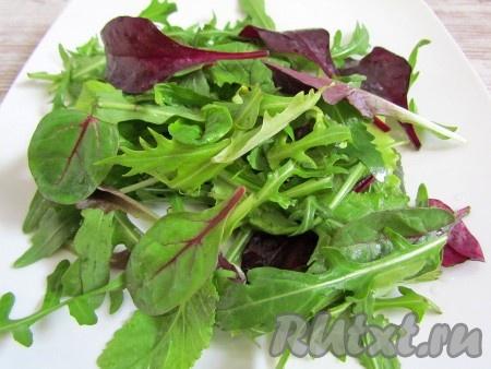 Салатные листья промойте, откиньте на дуршлаг и дайте воде стечь. Выложите листья на блюдо.