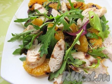 Сверху положите кусочки куриного мяса и мандариновые дольки. Полейте салат бальзамическим соусом и сразу же подавайте.