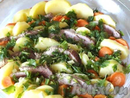 Смазываем сливочным маслом форму для запекания. Выкладываем вертикально слоями картофель, морковь и свинину. Сверху посыпаем порезанной петрушкой и зелёным луком.