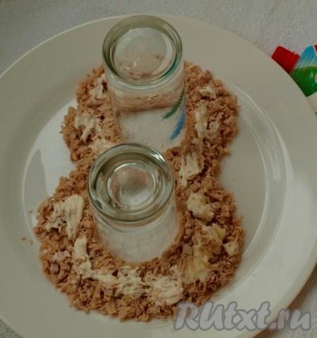 Нарезаем кубиками куриную грудку, чернослив и лук. Яйца разделяем на белки и желтки. Желтки натираем на мелкой тёрке, а белки оставляем для оформления. На плоскую тарелку ставим 2 стакана и выкладываем куриную грудку в виде цифры 8. Все слои смазываем майонезом.<br />