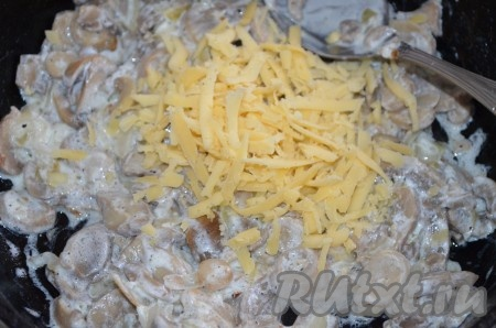 Натереть половину сыра и смешать с грибной начинкой.
