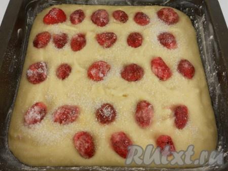 Форму смазать сливочным маслом, вылить в нее подготовленное тесто. Сверху разложить клубнику, посыпать щедро сахаром.
