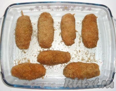 Куриные рулетики с начинкой из сыра и зелени выложить в форму для запекания и выпекать в духовке, разогретой до 180-190 градусов, 20-25 минут.