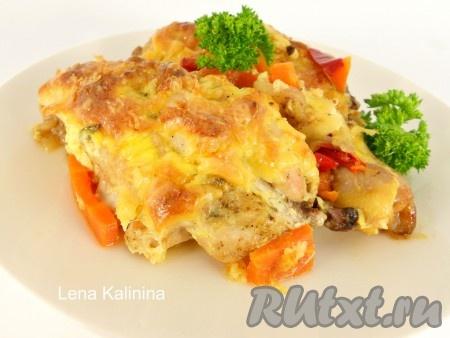 Выложить необыкновенно вкусную, нежную курицу под сыром, приготовленную в духовке, на тарелку вместе с овощами, украсить зеленью и подать в горячем виде к столу.