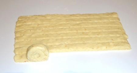 Охлаждённое тесто раскатать в пласт толщиной 5 мм, длиной примерно 30 см и нарезать на полоски шириной 1,5 см. Каждую полоску свернуть в рулет не до конца.